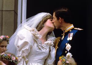 The Prince and Princess of Wales kiss on the balcony of Buckingham Palace after their wedding (PA)