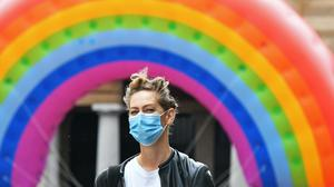 A woman wearing a face mask walks past a large rainbow in Covent Garden (PA)