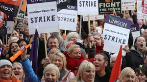 Strikers outside Glasgow Council's city chambers in George Square for a mass rally over equal pay (Andrew Milligan/PA)
