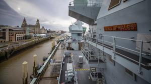 The Royal Navy aircraft carrier HMS Prince of Wales sits in front of the Royal Liver Building after it docked in Liverpool for a week-long visit to the city (Peter Byrne/PA)
