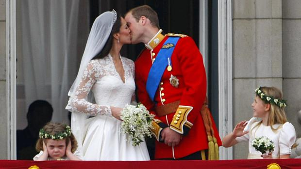 Prince William and his wife Kate Middleton kiss on the balcony as Grace van Cutsem covers her ears (Chris Ison/PA)