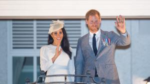 The Duke and Duchess of Sussex wave from a balcony during an overseas trip (PA)