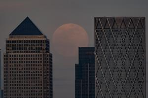 A pink supermoon is rises over Canary Wharf, London (Aaron Chown/PA)