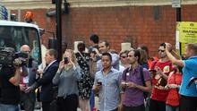 Members of the public take photos of the media outside St Mary's Hospital in London