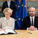 European Commission president Ursula von der Leyen and the president of the European Council, Charles Michel sign the Brexit agreement (European Commission/PA)