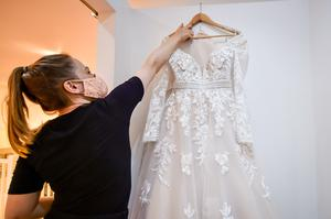 Bridal consultant Felicity Gray wears a face mask as she quarantines a wedding dress for 72 hours after sanitising it with disinfecting fabric spray (Ben Birchall/PA)