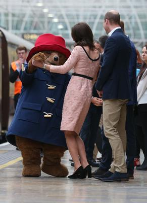 The Duke of Cambridge watches as his wife the Duchess of Cambridge dances with a costumed figure of Paddington bear (Jonathan Brady/PA)