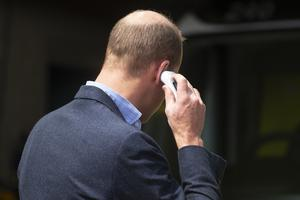 The Duke of Cambridge places a thermometer in his ear to check his temperature as he arrives at the ambulance station (Victoria Jones/PA)