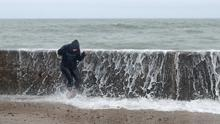 A person is hit by a wave crashing on the Front Strand in Youghal, Co. Cork, as Storm Ellen sweeps in