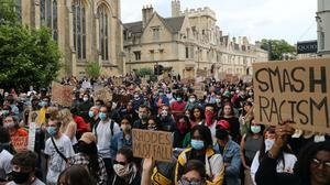 People during a protest calling for the removal of the statue of 19th century imperialist, politician Cecil Rhodes from an Oxford college which has reignited amid anti-racism demonstrations.