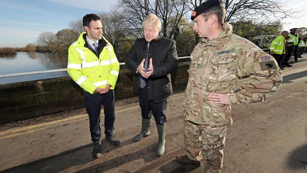 Boris Johnson walks with Lt Col Tom Robinson and Oliver Harmar of the Environment Agency (Danny Lawson/PA)