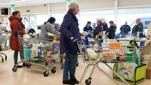 An elderly lady queues to pay for her shopping at a supermarket in Ashford, Kent (Gareth Fuller/PA)