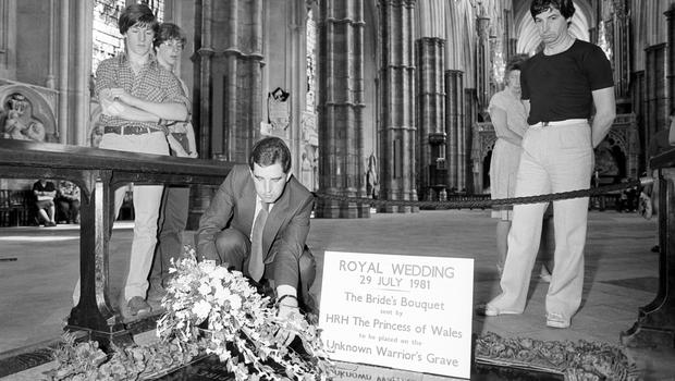 A registrar of Westminster Abbey gently lowering the Princess of Wales's bridal bouquet onto the Tomb of the Unknown Warrior (PA)