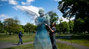Sculptor Luke Perry beside his winged medical worker (Jacob King/PA)