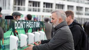Racegoers use hand sanitiser to keep their hands clean on day one of the Cheltenham Festival (Simon Cooper/PA)