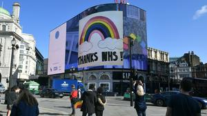 Members of the public take photographs of the Piccadilly Lights interactive mosaic art project, Rainbows For The NHS (Dominic Lipinski/PA Images)