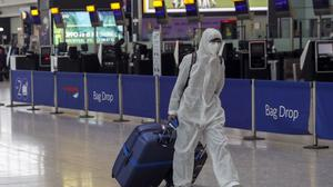 A passenger wearing protective clothing checks in for a flight from Heathrow Airport's Terminal 5 (Steve Parsons/PA)