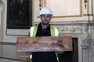Joe Hutchinson holding an uncovered roof board with an inscription etched into it from 1830 (Steve Mettam/Wentworth Woodhouse Preservation Trust)