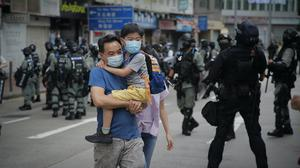 A man carries his son across a road before a line of riot police in Hong Kong (AP)