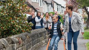 Tobias Weller is cheered on by neighbours as he walks along the street outside his home in Sheffield (Joe Giddens/PA)