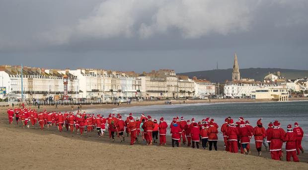 Hundreds of people dressed as Santa make their way along Weymouth beach, as they take part in the annual Chase the Pudding race (Andrew Matthews/PA)