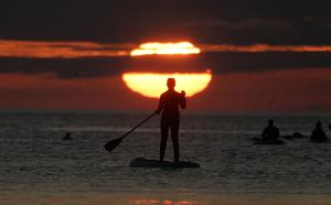 A paddleboarder watches the sunrise at Cullercoats bay in North Tyneside (Owen Humphreys/PA)