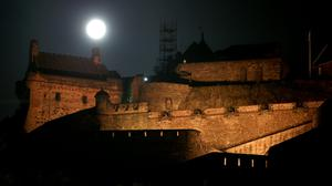 A full moon, known as a Sturgeon Moon in the month of August, rises behind Edinburgh Castle (Jane Barlow/PA)