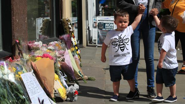 A woman and two young boys view tributes ahead of the Manchester Arena National Service of Commemoration at Manchester Cathedral (Peter Byre/PA)