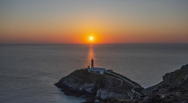 The sun sets behind South Stack lighthouse off the north-west coast of Holy Island, Anglesey, north Wales (Peter Byrne/PA)