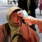 A health official scans the body temperature of a passenger as she arrives at Soekarno-Hatta International Airport in Tangerang, Indonesia (Tatan Syuflana/AP)