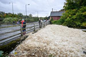 The River Neath is covered in foam from the extra water pouring over Aberdulais waterfall (Ben Birchall/PA)