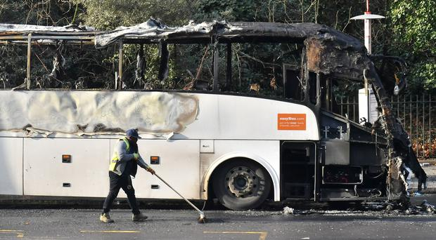 The burnt remains of a coach in Queenstown Road (Dominic Lipinski/PA)