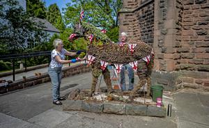 Wendy Doig and Roy Barker from St James Church in Woolton Village dress Jimmy the War Horse ahead of VE Day celebrations (Peter Byrne/PA)