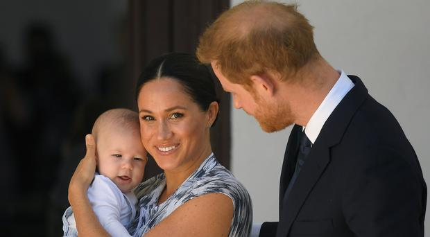 The Duke and Duchess of Sussex hold their son Archie during a meeting with Archbishop Desmond Tutu and Mrs Tutu at their legacy foundation in Cape Town (Toby Melville/PA)