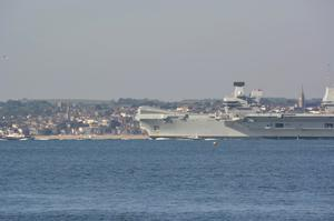 The Royal Navy aircraft carrier HMS Queen Elizabeth dwarfs Ryde on the Isle of Wight as it sails from anchor off Gosport, Hampshire, for sea trials on Friday, May 15 (Ben Mitchell/PA)