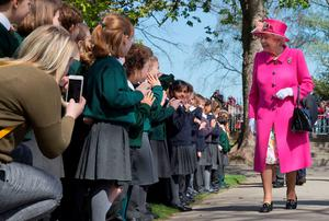 The Queen being greeted by schoolchildren as she arrives at the opening of the Alexandra bandstand