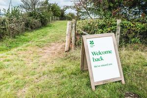 National Trust photo of a sign welcoming back visitors to the Lower Halsdon farm in Devon (Steve Sayers/PA)
