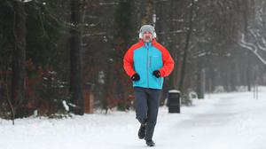 A man jogs down a snow covered street in Catterick, North Yorkshire (PA)