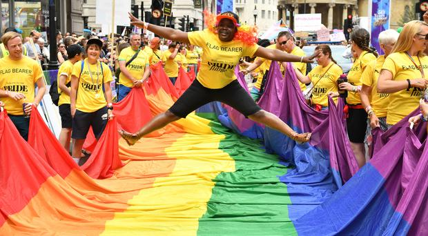 A flag bearer jumps above a rainbow flag ahead of the Pride in London Parade (Dominic Lipinski/PA)