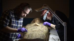 Conservators at Perth Museum and Gallery carefully clean a 3,000-year-old mummy Ta-Kr-Hb, nicknamed the Perth Mummy, and her sarcophagus (Julie Howden/Perth Museum and Art Gallery/PA)