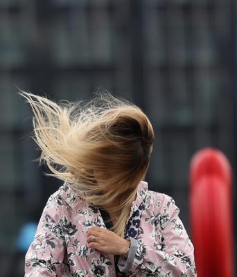 The wind catches a woman's hair in London as Storm Francis hit the UK on August 25 (Yui Mok/PA)