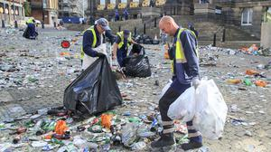 Workers clear litter in the centre of Leeds after celebrations by fans whose football club won the Championship title and a return to the Premier League (Danny Lawson/PA)
