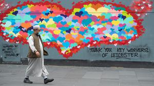A man wearing a protective face mask walks past artwork in Leicester (Joe Giddens/PA)
