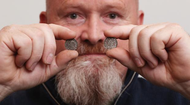 Builder and metal detectorist Don Crawley holds two particularly rare Anglo Saxon silver pennies. The hoard of 99 silver coins sold for £90,000 at auction (Jonathan Brady/ PA)