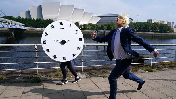 A man dressed as Prime Minister Boris Johnson races against a clock in Glasgow in the charity stunt (Andrew Milligan/PA)