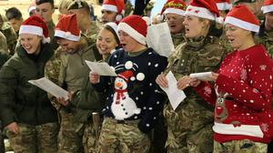 Military personnel don Santa hats and Christmas jumpers as they sing carols in Afghanistan (MoD/PA)