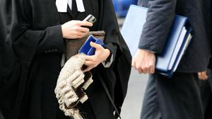 A barrister carries a wig into the Royal Courts of Justice (Katie Collins/PA)