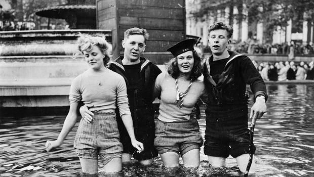 Joyce Digney (left) and Cynthia Covello, photographed celebrating VE Day with two sailors in a fountain in Trafalgar Square