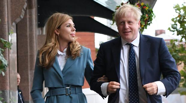 Prime Minister Boris Johnson arrives, accompanied by partner Carrie Symonds, ahead of the Conservative Party Conference in Manchester, as the Tories have insisted it will go ahead despite the Commons voting against the Government's request for a three-day recess to coincide with the event (PA)