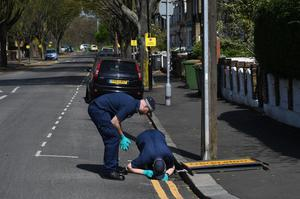 Police search a drain in Chestnut Avenue after the fatal stabbing (Stefan Rousseau/PA)